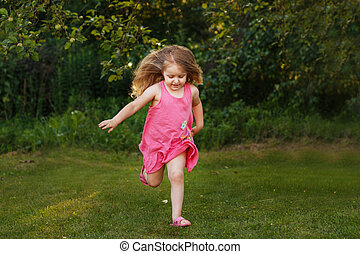 happy baby smiling. little girl running at a sunset outdoor