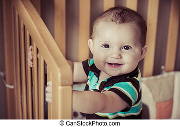 Happy baby standing up in his crib in image with vintage filter