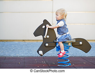 Happy baby swinging on horse on playground. Side view