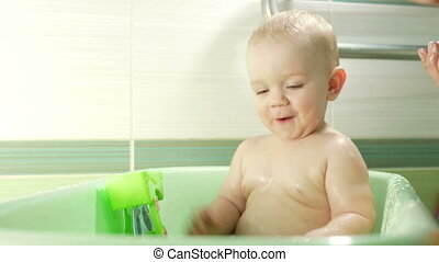 Happy baby taking a bath playing with foam bubbles. Mother washing little boy. Young child in a bathtub. Smiling kids in bathroom with toys. Parent and kid play with water.