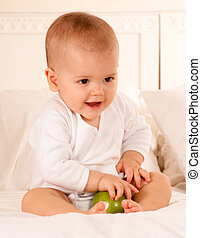 happy baby with apple - Cute baby on a bodysuit holding a...