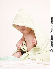 Happy baby with green towel.Age of 8 months. It is isolated...