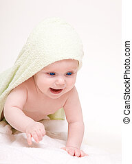Happy baby with green towel.Age of 8 months.