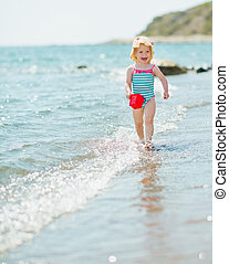 Happy baby with pail running along seashore