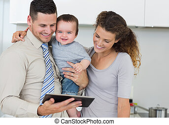 Happy baby with parents using digital tablet