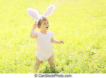 Happy baby with rabbit ears in sunny summer day