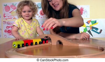 Happy babysitter and toddler child girl play with wooden train in kindergarten