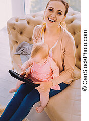 Happy babysitter laughing while seeing a baby using her modern tablet
