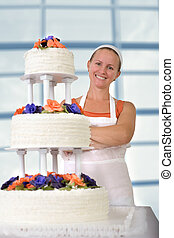 Happy Baker Lady smiling infront of her Ruffled Wedding Cake