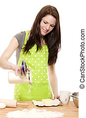 happy baking woman pouring flour on a table with white background