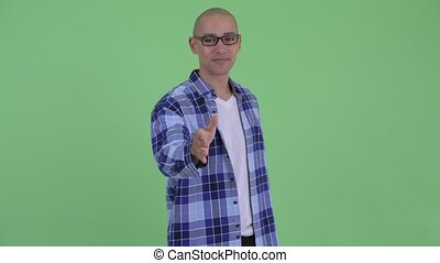 Happy bald hipster man giving handshake - Studio shot of...