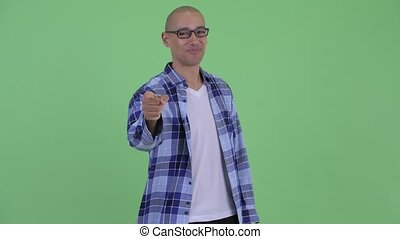Happy bald hipster man pointing at camera - Studio shot of...
