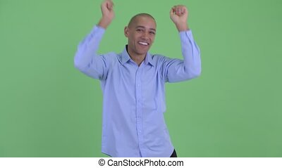 Happy bald multi ethnic businessman dancing