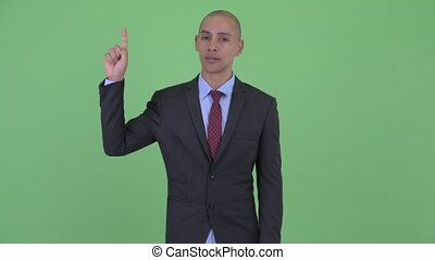 Happy bald multi ethnic businessman pointing up - Studio...