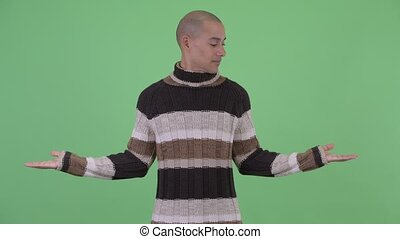 Happy bald multi ethnic man comparing something - Studio...