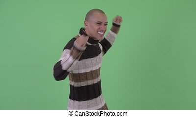 Happy bald multi ethnic man dancing ready for winter