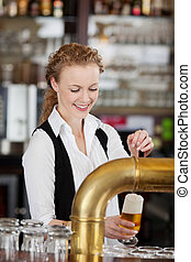 Happy barmaid pouring draft beer