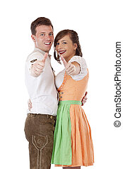 Happy Bavarian man and woman with dirndl holds thumbs up