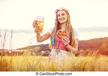 Happy Bavarian woman with beer and traditional food in summer