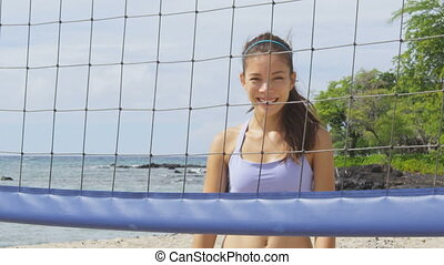Happy beach volleyball woman player. Portrait of smiling woman behind beach volley ball net looking at camera. Mixed race Asian Caucasian woman athlete. RED EPIC SLOW MOTION.