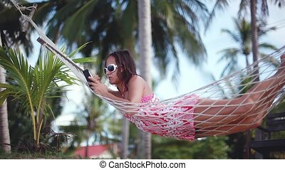 Happy beach woman reading sms texting on smartphone lying on...