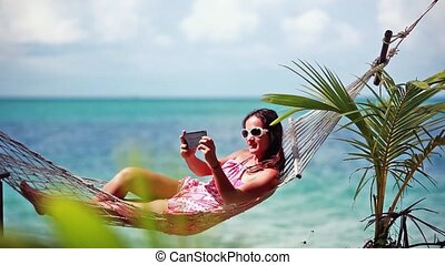 Happy beach woman wearing sunglasses taking selfie with...