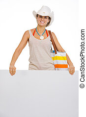 Happy beach young woman showing blank billboard