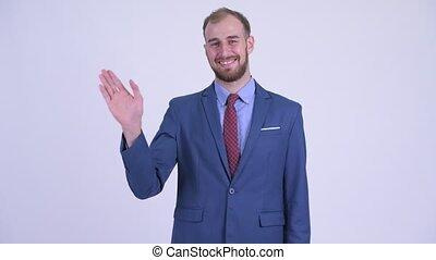 Happy bearded businessman in suit waving hand