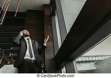 Happy bearded businessman talking on mobile indoor
