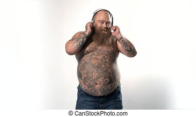 Happy bearded fatty listening to music and dancing