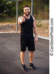 Happy bearded fitness man showing thumb up outdoors