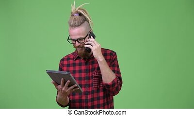Happy bearded hipster man with dreadlocks talking on the...