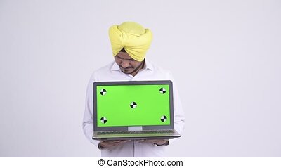 Happy bearded Indian Sikh businessman showing laptop -...