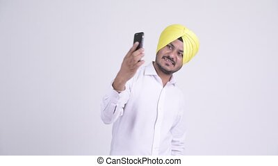 Happy bearded Indian Sikh businessman video calling with...