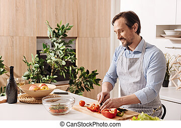 Happy bearded man cooking salad in the kitchen