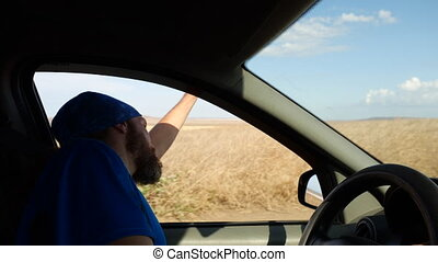 Happy bearded man drives a car in rural landscape. Driver waves hand leaning out of the side window