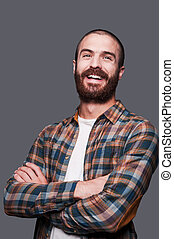 Happy bearded man. Handsome young bearded man keeping arms crossed and smiling while standing against grey background