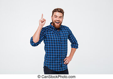 Happy bearded man pointing finger up and having an idea