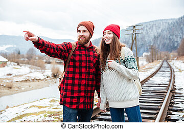 Happy bearded man standing and showing direction to his girlfriend
