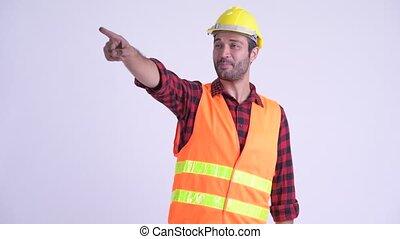 Studio shot of handsome bearded Turkish man construction worker against white background