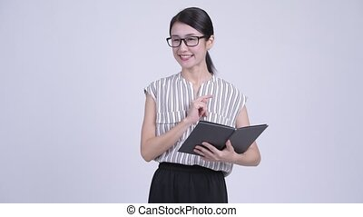 Happy beautiful Asian businesswoman as teacher talking and reading book