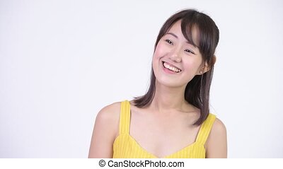 Happy beautiful Asian woman smiling and thinking - Studio...