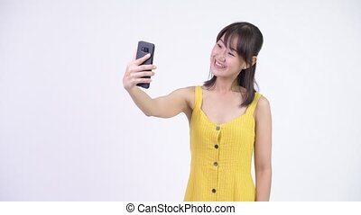 Happy beautiful Asian woman taking selfie with phone -...
