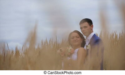 happy beautiful bride and groom on field