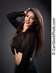 Happy beautiful brunette woman with long hair style in fashion black shirt looking with toothy smiling on dark shadow background
