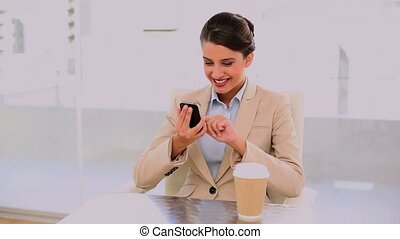 Happy beautiful businesswoman drinking coffee while using mobile phone at office