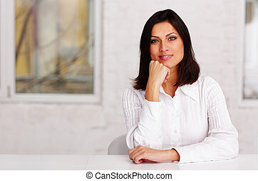 Happy beautiful businesswoman sitting at the table in office