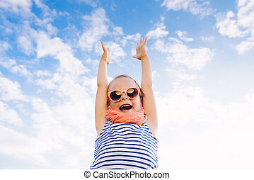 Happy beautiful child girl in sunglasses with raised arms against the sky