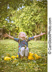 happy beautiful child throwing leaves