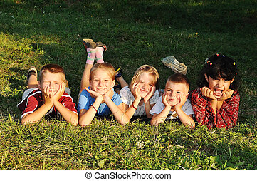 Happy beautiful children laying on ground outdoor